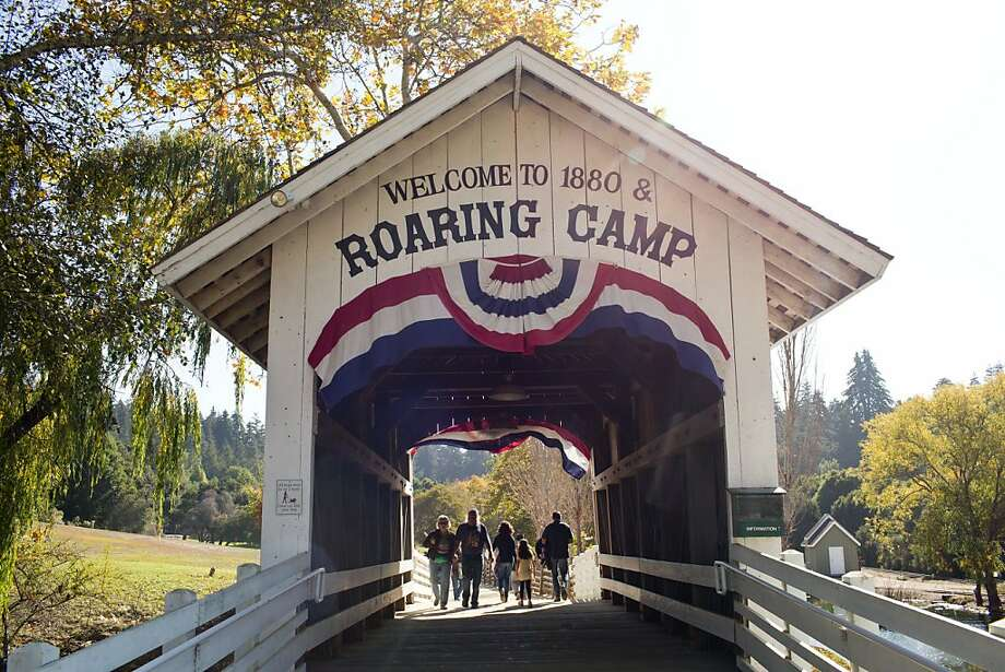 A covered bridge leads to Roaring Camp, where trains depart for a ride through redwoods or to Santa Cruz. The Holiday Lights trips begin at the boardwalk. Photo: Jason Henry, Special To The Chronicle