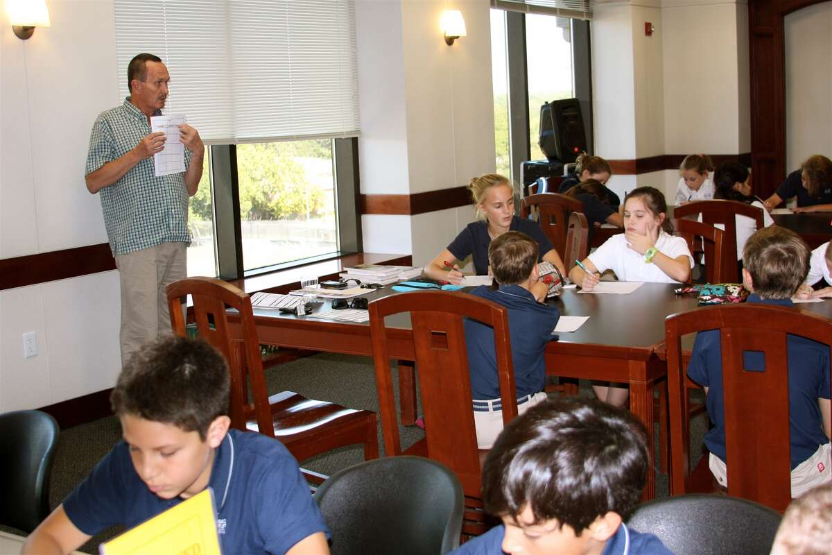 """Author Dave Gustaveson tells students at Second Baptist School about his """"Reel Kids Adventure"""" series."""