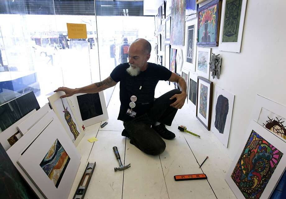 Ivan Vera hangs artwork in the Hospitality House Community Art Program window on Market Street. Photo: Paul Chinn, The Chronicle