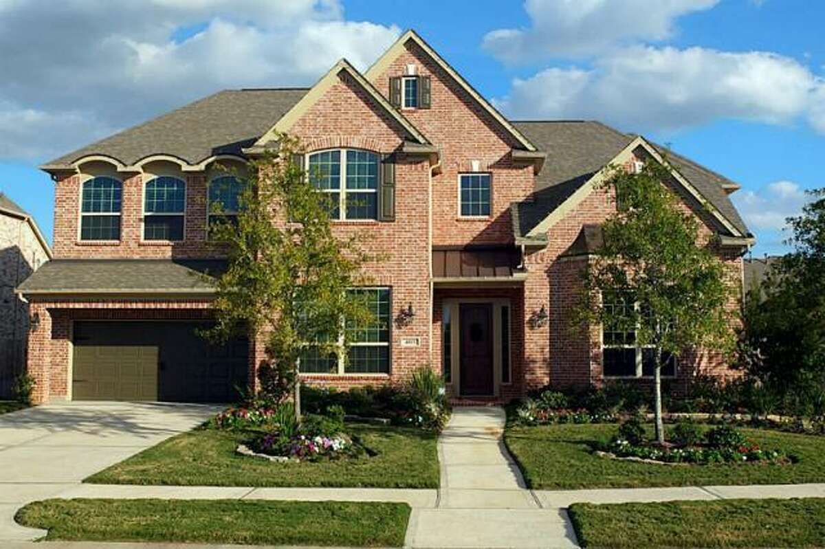 The home features beautiful landscaping and a brick exterior.