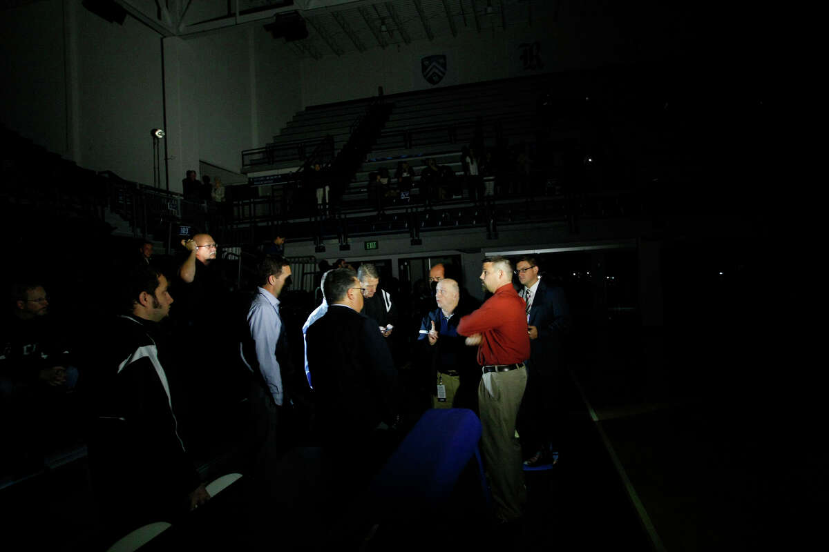 Officials work to get the game started after the power went out in the Tudor Field House at Rice University Tuesday, Nov. 12, 2013, in Houston. The Owls were set to take on the Southeastern Louisiana Lions until the power went off just before tip off. Officials are working to determine the source.