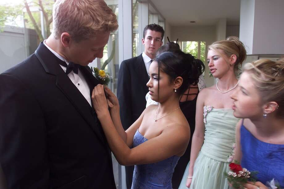 Roosevelt prom, 2000. (Janelle Velasquez pins a boutonniere on prom date Andy Moering, as friends look on). Photo: MIKE URBAN, P-I File