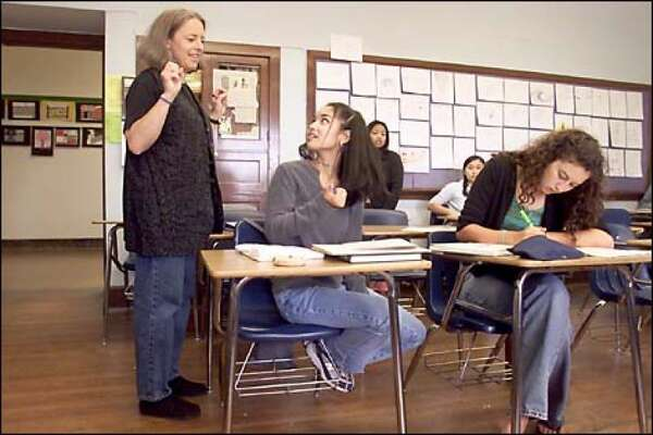 Janelle Velasquez listens as her English teacher, Ms. Oas, outlines the agenda for the senior class' last day of instruction at Seattle's Roosevelt High School.
