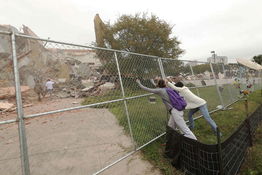 Protesters attempt to take a fence down at the former Univision building after Judge Janet Littlejohn ruled to dissolve a temporary restraining order, Tuesday, Nov. 12, 2013. It cleared the way for demolition to continue. It cleared the way for demolition to continue. Developing company, Greystar, plans on building a $55-million 355-unit apartment on the site. Eight protesters were arrested trying to stop the demolition.
