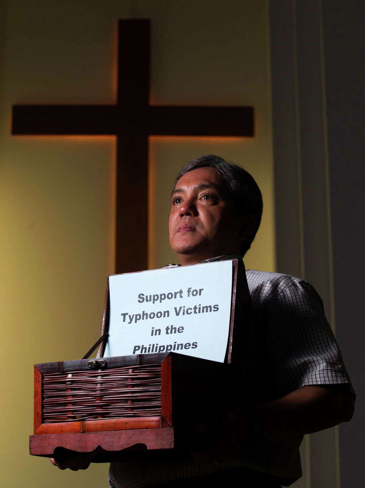 Executive pastor of Houston's First Philippine Baptist Church Dr. Ernest Howard Dagohoy recently posed for a portrait with a collection box to help victims of Typhoon Haiyan in the Philippines. He and volunteers from his church were planning to go to the Philippines to help with relief efforts. ( J. Patric Schneider / For the Chronicle )