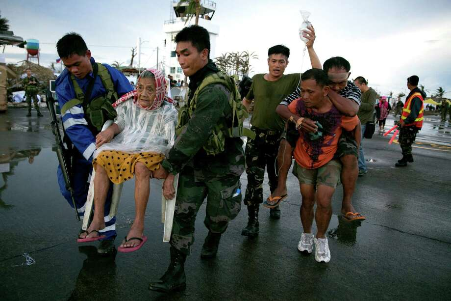 An elderly woman and an injured man are carried to a waiting aircraft during the evacuation of hundreds of typhoon survivors  in Tacloban, Philippines. Photo: Paula Bronstein / Getty Images