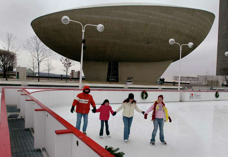 TIMES UNION PHOTO BY LUANNE M. FERRIS        Sunday, Dec. 26, 2004, Albany, NY, Open skating at the Empire State Plaza Ice Rink with the Egg, looming in the background.  Family and friends enjoy a day at the rink.   L-R: Sergio Garufi, his daughter Angie, age 9, just learning to skate, his wife Melissa Garufi, all of Loudonville,  and a friend Laura Loudis, of Colonie, age 12. Photo: LUANNE M. FERRIS / TIMES UNION