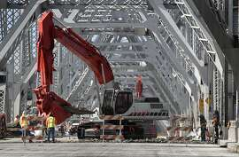 Heavy machinery removes a section of roadway as demolition work begins on the old eastern span of the Bay Bridge in Oakland, Calif. on Tuesday, Nov. 12, 2013. If all goes as planned, the deconstruction work is scheduled to be completed by late 2016