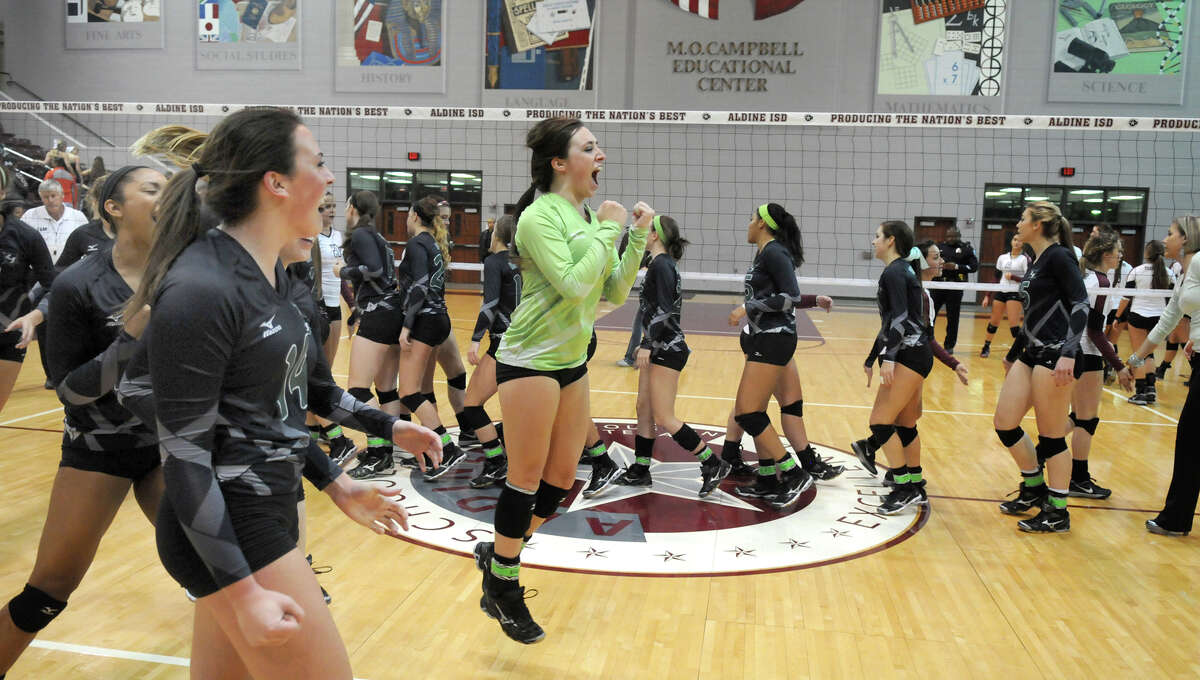 Clear Falls senior libero Morgan St. Germain, center, and junior outside hitter Alyssa Enneking, in foreground, celebrate the Kinight's three set win over the Pearland Oilers in their Region III-5A Regional Quarterfinal match at the Campbell Center on Tuesday.