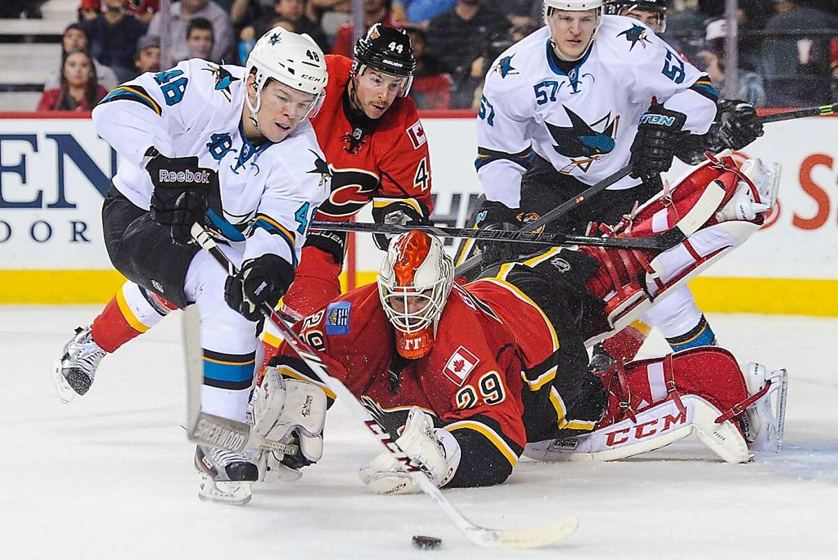 CALGARY, AB - NOVEMBER 12: Reto Berra #29 of the Calgary Flames eyes the loose puck in front of Tomas Hertl #48 of the San Jose Sharks during an NHL game at Scotiabank Saddledome on November 12, 2013 in Calgary, Alberta, Canada. (Photo by Derek Leung/Getty Images)