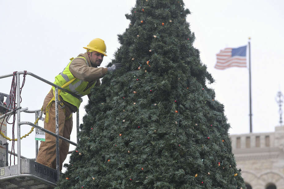 Ben Becker with the city of New Braunfels' Parks Department works high above the ground in cold and windy conditions as Christmas decorations are installed in the town square Tuesday. Photo: Tom Reel / San Antonio Express-News
