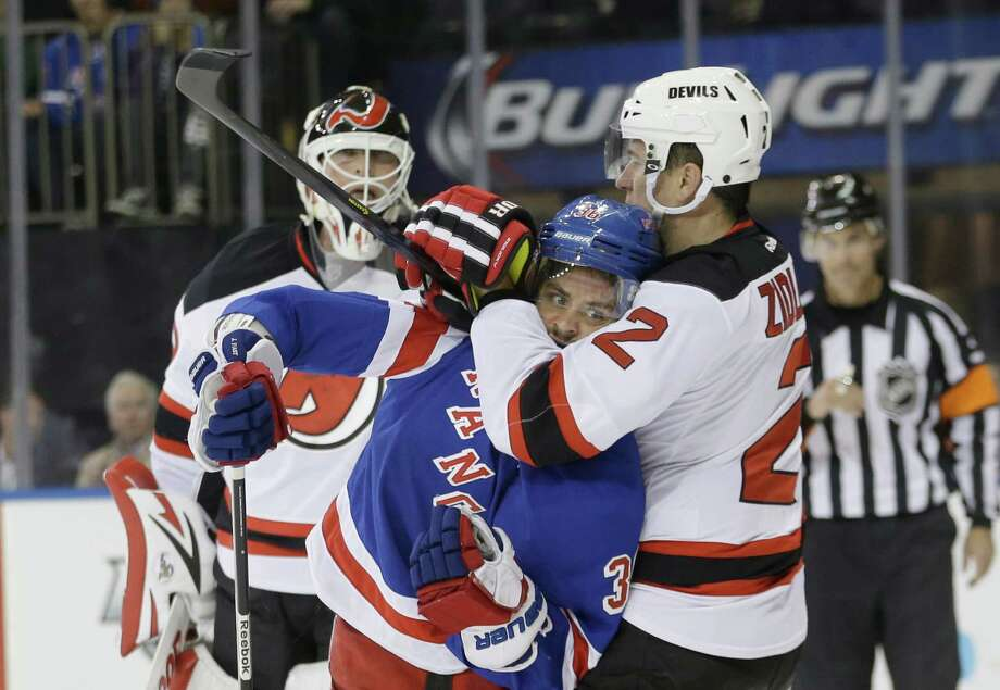 New Jersey Devils' Marek Zidlicky (2) grabs New York Rangers' Mats Zuccarello (36) as Devils goalie Martin Brodeur watches during the second period of an NHL hockey game Tuesday, Nov. 12, 2013, in New York. (AP Photo/Frank Franklin II) ORG XMIT: MSG110 Photo: Frank Franklin II / AP