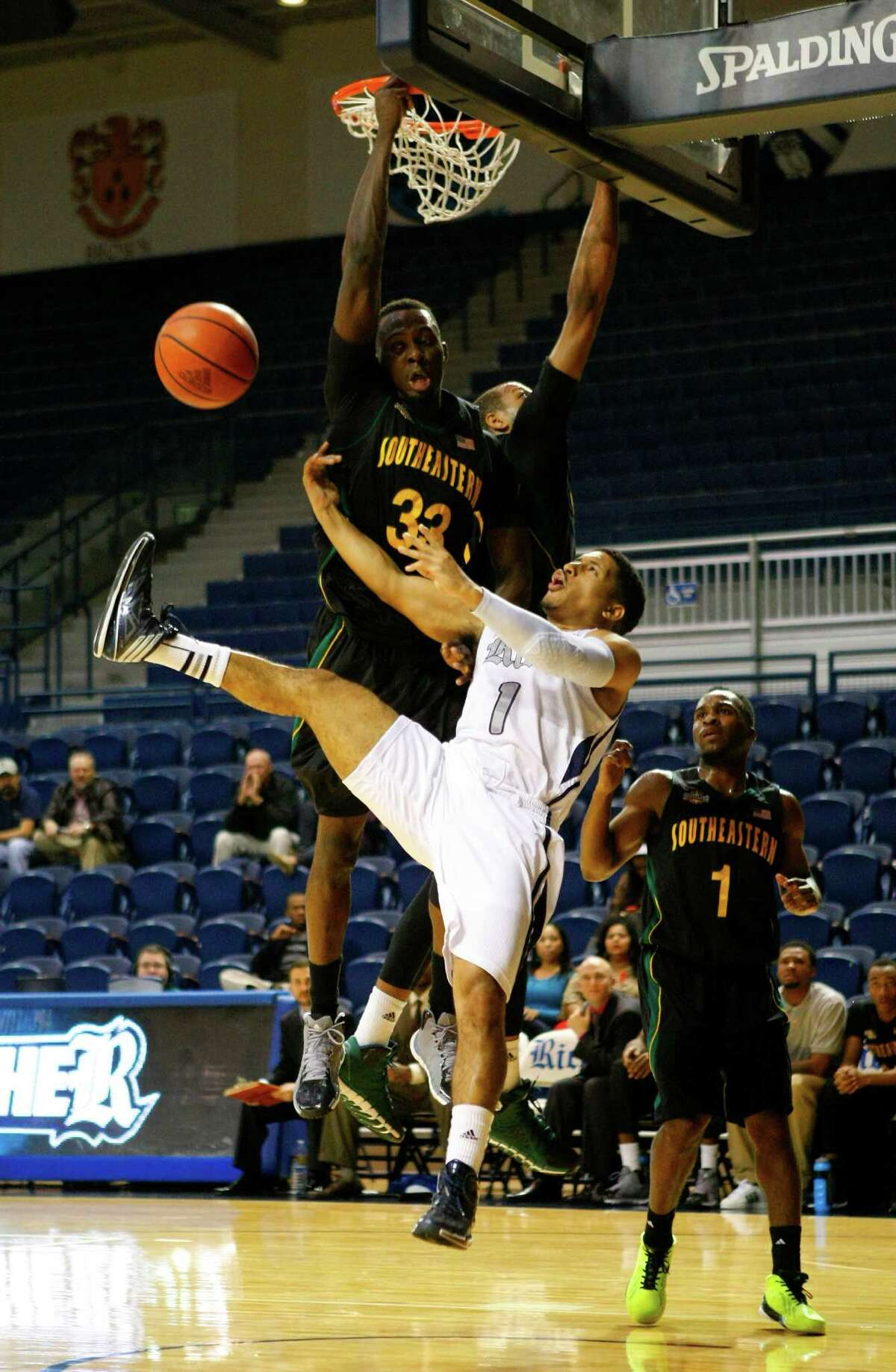 Rice guard Max Guercy takes a hit from Southeastern Louisiana's Onochie Ochie during the Owls' loss.