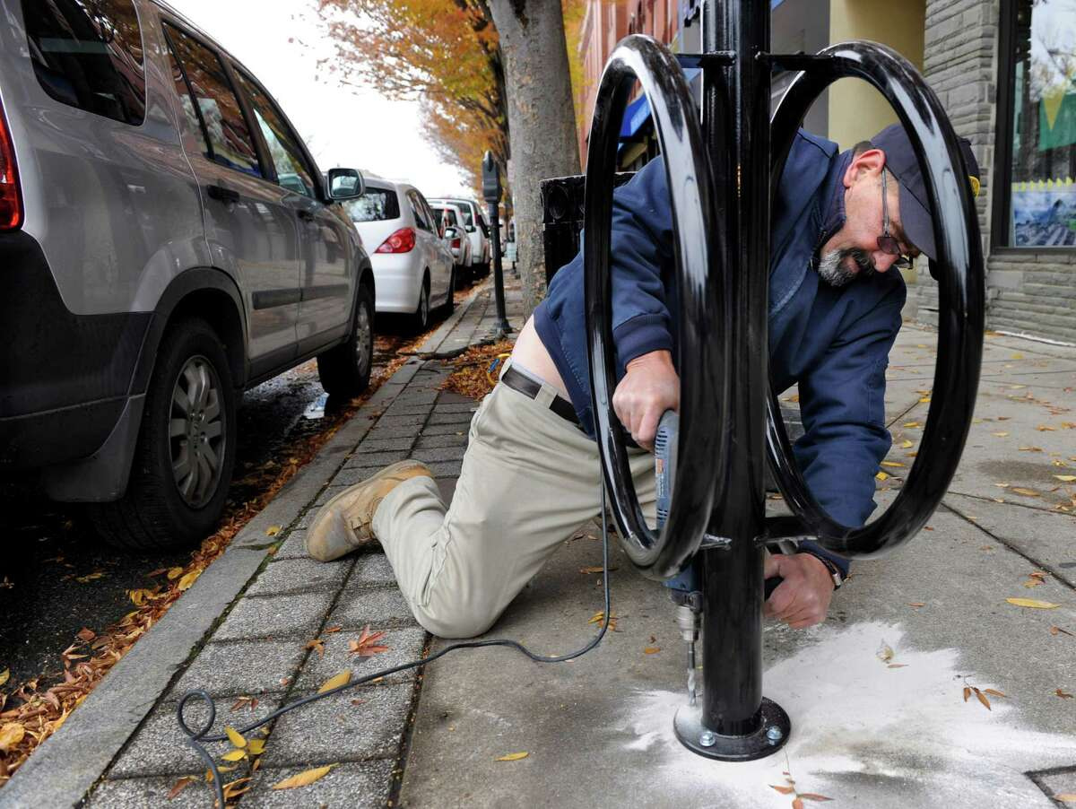 Robert Ambrose, an employee with the Danbury Parking Authority, installs one of four bicycle racks in the downtown area Tuesday, Nov. 12, 2013.