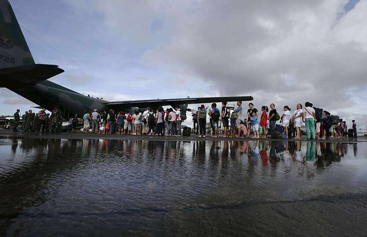 Typhoon survivors prepare to board a military transport plane Wednesday Nov. 13, 2013 from the damaged Tacloban airport in Tacloban city, Leyte province in central Philippines. Typhoon Haiyan, one of the strongest storms on record, slammed into central Philippine provinces Friday, leaving a wide swath of destruction and thousands of people dead.(AP Photo/Bullit Marquez)