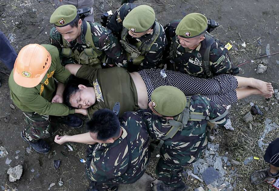 Soldiers rush a typhoon survivor after she collapsed in a queue to board a military transport plane Wednesday Nov. 13, 2013 from the damaged Tacloban airport  in Tacloban city, Leyte province in central Philippines. Typhoon Haiyan, one of the strongest storms on record, slammed into central Philippine provinces Friday, leaving a wide swath of destruction and thousands of people dead. (AP Photo/Bullit Marquez) Photo: Bullit Marquez, Associated Press