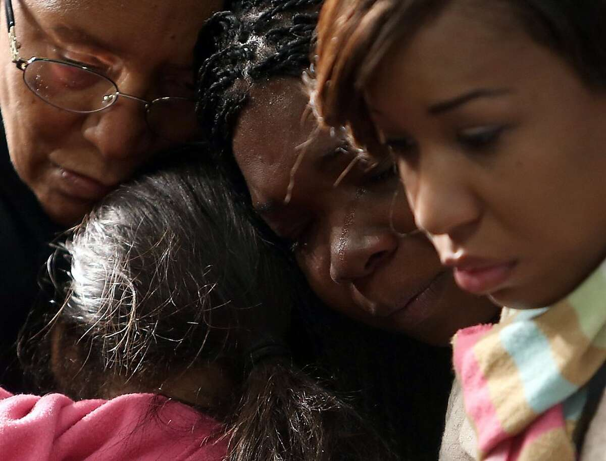November 12, 2013 DeKalb County: Aunt Verdette Bagley, left, cousin Brooklynn Kirkland, second from left, friend Kesia Lee and aunt Dalexia Bagley, right. comfort each other during a prayer vigil for Emani Moss Tuesday evening, Nov. 12, 2013 at the Greater Travelers Rest Baptist Church in DeKalb County. Ga. Emani Moss was found dead, her body burned, in a trash bin early Saturday morning, Nov. 2, 2013. (AP Photo/Atlanta Journal-Constitution, Ben Gray) MARIETTA DAILY OUT; GWINNETT DAILY POST OUT; LOCAL TV OUT; WXIA-TV OUT; WGCL-TV OUT