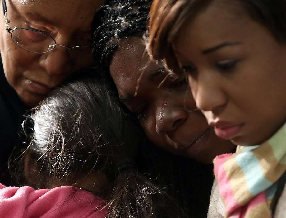 November 12, 2013 DeKalb County: Aunt Verdette Bagley,  left, cousin Brooklynn Kirkland, second from left, friend Kesia Lee and aunt Dalexia Bagley, right. comfort each other during a prayer vigil for Emani Moss Tuesday evening, Nov. 12, 2013 at the Greater Travelers Rest Baptist Church in DeKalb County. Ga. Emani Moss was found dead, her body burned, in a trash bin early Saturday morning, Nov. 2, 2013.    (AP Photo/Atlanta Journal-Constitution, Ben Gray)  MARIETTA DAILY OUT; GWINNETT DAILY POST OUT; LOCAL TV OUT; WXIA-TV OUT; WGCL-TV OUT Photo: Ben Gray, Associated Press