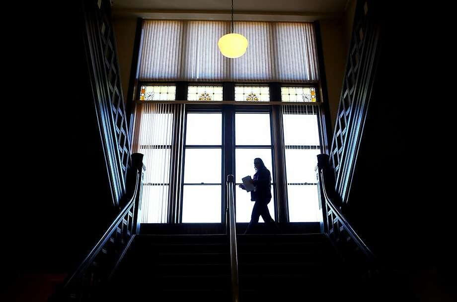 A woman is silhouetted as she walks down a staircase at the Dubuque, Iowa County Courthouse Tuesday, Nov. 12, 2013. (AP Photo/The Telegraph Herald, Jeremy Portje) Photo: Jeremy Portje, Associated Press