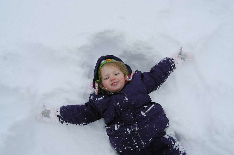 Madison Molineaux, 3, creates a snow angel outside her home in St. Joseph, Mich., Tuesday, Nov. 12, 2013, after a fall snowstorm. (AP Photo/The Herald-Palladium, Don Campbell) Photo: Don Campbell, Associated Press
