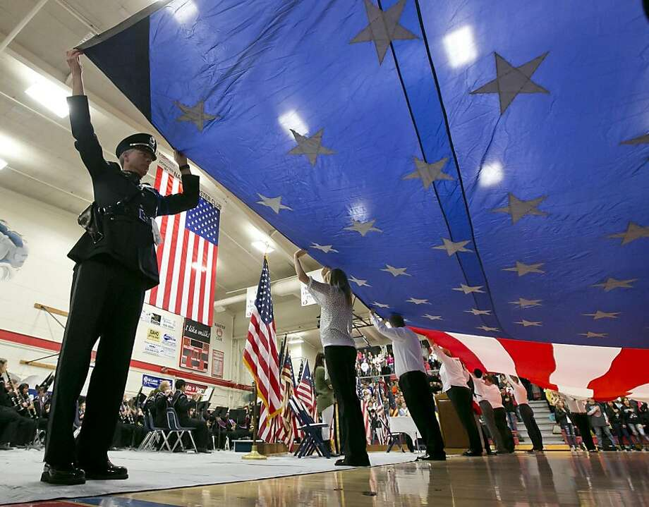 Nampa High students and other civic representatives honor veterans during a special Veterans Day assembly that included the unfurling of a giant U.S. Flag Tuesday, Nov. 12, 2013 in Nampa, Idaho. (AP Photo/The Idaho Statesman, Darin Oswald)  LOCAL TV OUT (KTVB 7) Photo: Darin Oswald, Associated Press