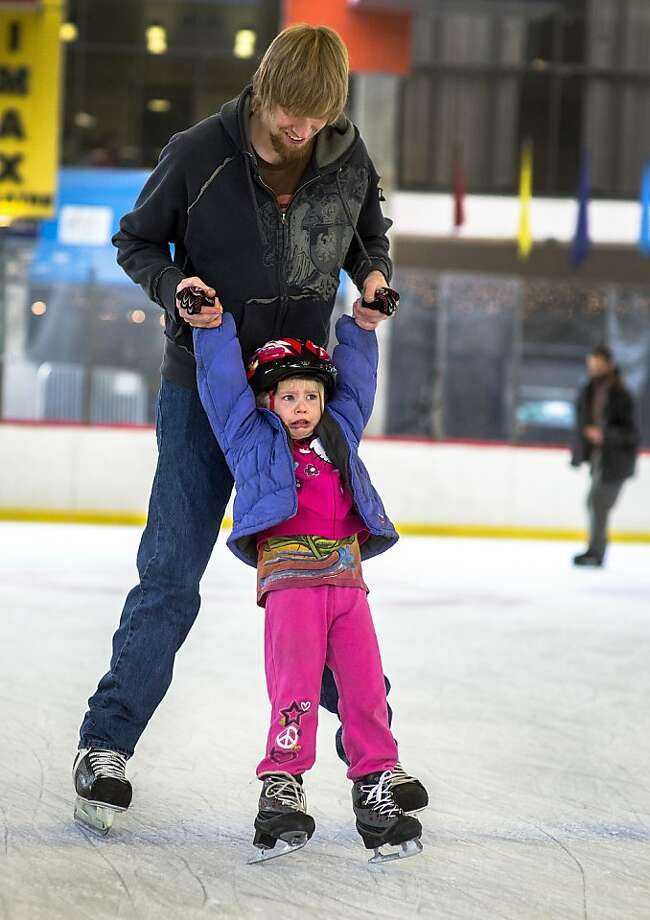 Ice 'fallies': Despite dad Nathan's encouraging words, 4-year-old Candace Vantine isn't enjoying her first day on skates in Spokane, Wash. Photo: Colin Mulvany, Associated Press