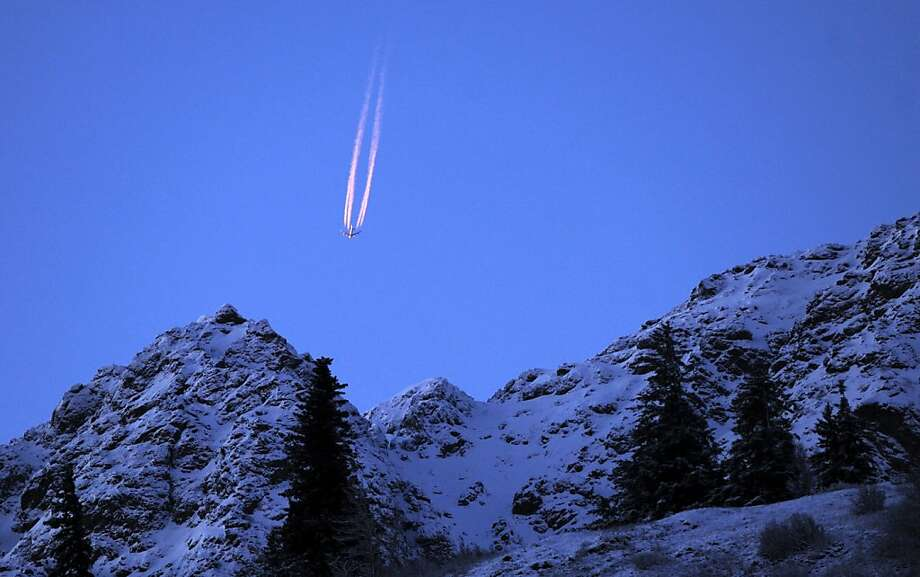 A passing jet plane catches sunset light above the darkening Chugach Mountains on late Monday Nov. 11, 2013, in a view from the Seward Highway along Turnagain Arm near Anchorage, Alaska. (AP Photo/Anchorage Daily News, Erik Hill) LOCAL TV OUT (KTUU-TV, KTVA-TV) LOCAL PRINT OUT (THE ANCHORAGE PRESS, THE ALASKA DISPATCH) Photo: Erik Hill, Associated Press