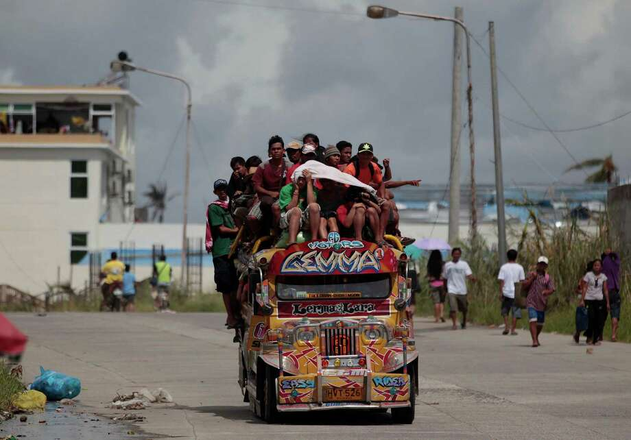 Survivors ride an overloaded passenger jeepney as they flee typhoon-hit Tacloban city, Leyte province, central Philippines on Wednesday, Nov. 13, 2013. Typhoon Haiyan, one of the strongest storms on record, slammed into six central Philippine islands on Friday leaving a wide swath of destruction. Photo: Aaron Favila, AP / AP