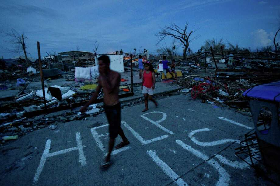 Typhoon Haiyan survivors walk through the ruins of their neighborhood in Tacloban, central Philippines on Wednesday, Nov. 13, 2013. A man named J.R. Apan painted a plea for help in front of his destroyed home the day after the typhoon hit hoping for aid to arrive but says he has not yet received food and water supplies. Photo: David Guttenfelder, AP / AP