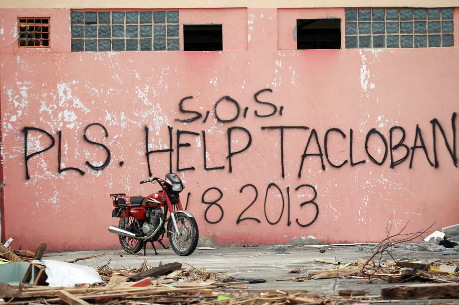 A message seeking help is written on the wall of destroyed building  by residents on November 13, 2013 in Tacloban, Leyte, Philippines. Typhoon Haiyan, packing maximum sustained winds of 195 mph (315 kph), slammed into the southern Philippines and left a trail of destruction in multiple provinces, forcing hundreds of thousands to evacuate and making travel by air and land to hard-hit provinces difficult. Around 10,000 people are feared dead in the strongest typhoon to hit the Philippines this year. Photo: Jeoffrey Maitem, Getty Images / 2013 Getty Images