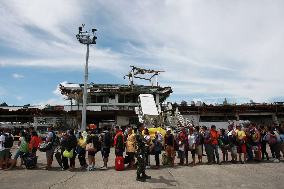 Residents bound for Manila prepare to board a C-130 plane on November 13, 2013 in Tacloban, Leyte, Philippines. Typhoon Haiyan, packing maximum sustained winds of 195 mph (315 kph), slammed into the southern Philippines and left a trail of destruction in multiple provinces, forcing hundreds of thousands to evacuate and making travel by air and land to hard-hit provinces difficult. Around 10,000 people are feared dead in the strongest typhoon to hit the Philippines this year. Photo: Jeoffrey Maitem, Getty Images / 2013 Getty Images