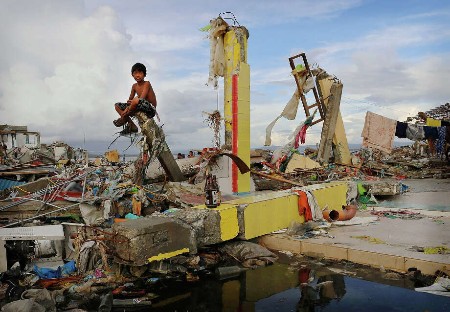A young boy sits on the ruins of a building amid scenes of devastation in the aftermath of Typhoon Haiyan on November 13, 2013 in Tacloban, Leyte, Philippines. Typhoon Haiyan, packing maximum sustained winds of 195 mph (315 kph), slammed into the southern Philippines and left a trail of destruction in multiple provinces, forcing hundreds of thousands to evacuate and making travel by air and land to hard-hit provinces difficult. Around 10,000 people are feared dead in the strongest typhoon to hit the Philippines this year. Photo: Kevin Frayer, Getty Images / 2013 Getty Images