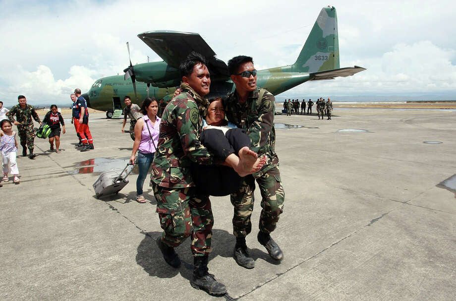 Soldiers carry an elderly woman as US marines prepare relief for people affected in the aftermath of Typhoon Haiyan on November 13, 2013 in Tacloban, Leyte, Philippines. Typhoon Haiyan, packing maximum sustained winds of 195 mph (315 kph), slammed into the southern Philippines and left a trail of destruction in multiple provinces, forcing hundreds of thousands to evacuate and making travel by air and land to hard-hit provinces difficult. Around 10,000 people are feared dead in the strongest typhoon to hit the Philippines this year. Photo: Jeoffrey Maitem, Getty Images / 2013 Getty Images