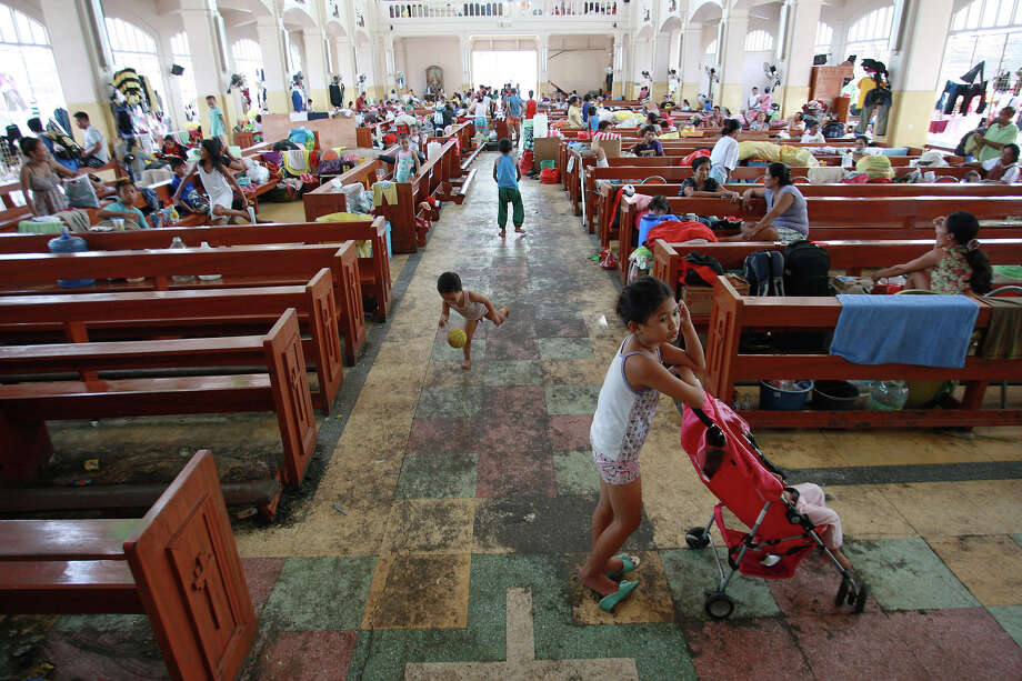 Residents take shelter in a church amid scenes of devastation in the aftermath of Typhoon Haiyan on November 13, 2013 in Tacloban, Leyte, Philippines. Typhoon Haiyan, packing maximum sustained winds of 195 mph (315 kph), slammed into the southern Philippines and left a trail of destruction in multiple provinces, forcing hundreds of thousands to evacuate and making travel by air and land to hard-hit provinces difficult. Around 10,000 people are feared dead in the strongest typhoon to hit the Philippines this year. Photo: Jeoffrey Maitem, Getty Images / 2013 Getty Images