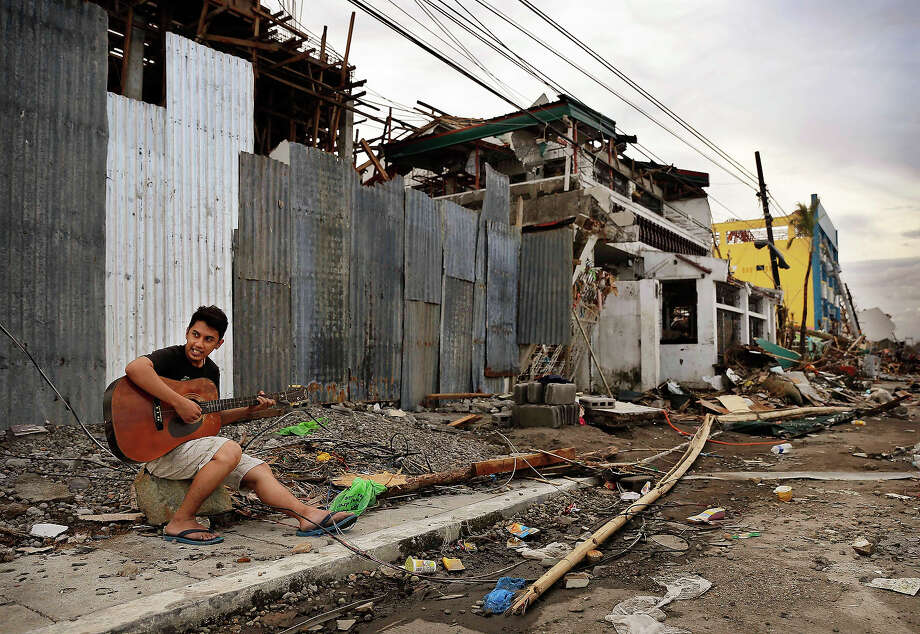 A Filipino man plays guitar amid scenes of devastation in the aftermath of Typhoon Haiyan on November 13, 2013 in Tacloban, Leyte, Philippines. Typhoon Haiyan, packing maximum sustained winds of 195 mph (315 kph), slammed into the southern Philippines and left a trail of destruction in multiple provinces, forcing hundreds of thousands to evacuate and making travel by air and land to hard-hit provinces difficult. Around 10,000 people are feared dead in the strongest typhoon to hit the Philippines this year. Photo: Kevin Frayer, Getty Images / 2013 Getty Images