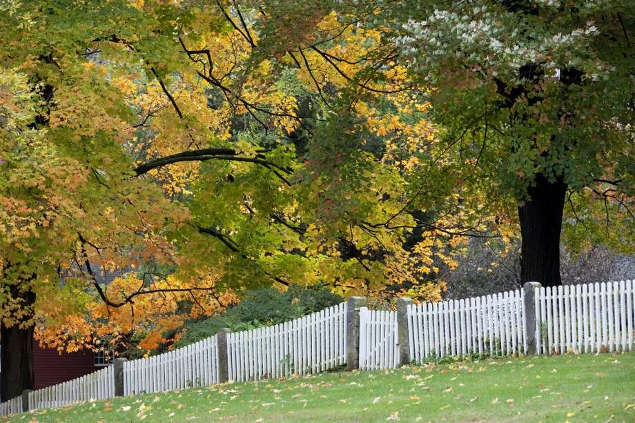 The leaves on the trees have turned orange, yellow and red in the fall, contrasting with a white picket fence in this historic town, on October 7, 2013 in Deerfield, Massachusetts. Photo: Christian Science Monitor, Melanie Stetson Freeman/The Christian Science Monitor Via Getty Images