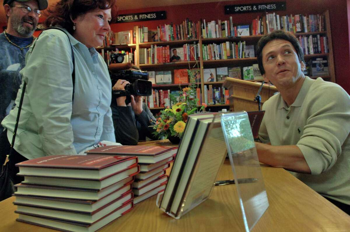 """Times Union Staff photograph by Philip Kamrass Best selling author Mitch Albom, right, signs one of his books for fan Christine Van Ullen of Cohoes, left, at the Borders book store in Colonie, NY Thursday September 28, 2006. Albom's new book """"For One More Day"""" prompted Van Ullen to tell Albom that she almost lost her 82 year old mom to heart surgery earlier in the year, and intended to give a signed copy of the book to her mom, who is also an Albom fan. Albom's new book is about what one would say to deceased friends and relatives if given another chance."""