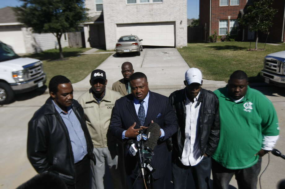 Quanell X addresses the media outside the home of where the fatal house party took place in Cypress with the two fathers of the victims.  Lawrence  Guidry, whose son Queric Richardson died and Terrence Shepherd, whose daughter Arielle Shepherd died. Photo: Johnny Hanson, Houston Chronicle