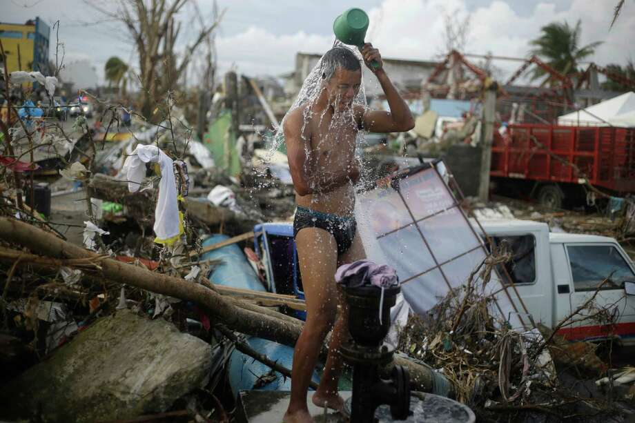 A man takes a shower amid rubble in an area badly affected by Typhoon Hayan in Tacloban, central Philippines, Wednesday, Nov. 13, 2013. Typhoon Haiyan, one of the strongest storms on record, slammed into six central Philippine islands on Friday, leaving a wide swath of destruction. Photo: Dita Alangkara, Associated Press / AP2013