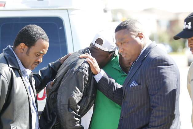 Quanell X and Terrence Shepherd, whose daughter Arielle Shepherd died comfort  Lawrence  Guidry, whose son Queric Richardson died after he saw blood stains on the pavement outside the home of where the fatal house party took place in Cypress . Photo: Johnny Hanson