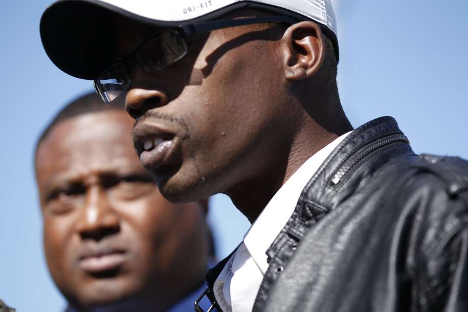 Lawrence  Guidry, whose son Queric Richardson died in the Cypress house party shooting, speaks Wednesday, Nov. 11, 2013 in front of the house where the shooting took place. Community organizer Quanell X listens in the background. Photo: Johnny Hanson, Houston Chronicle