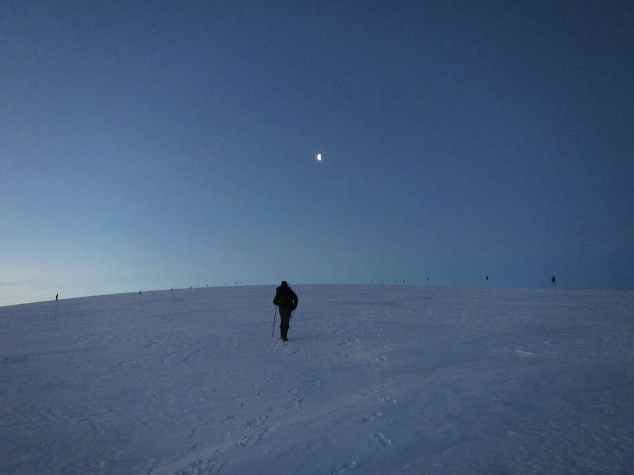 A photo from the Woods Hole Oceanographic Institution blog shows the hours-long Antarctica twilight. Researcher Greg Roberts makes his way up the glacier toward the rising moon. (Jamie Collins/ http://web.whoi.edu/coldsuncommunication/)