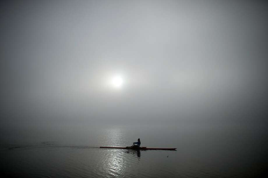 Single scull: A solo rower strokes across Lake Baldeneysee on a foggy morning in Essen, Germany. Photo: Federico Gambarini, Associated Press