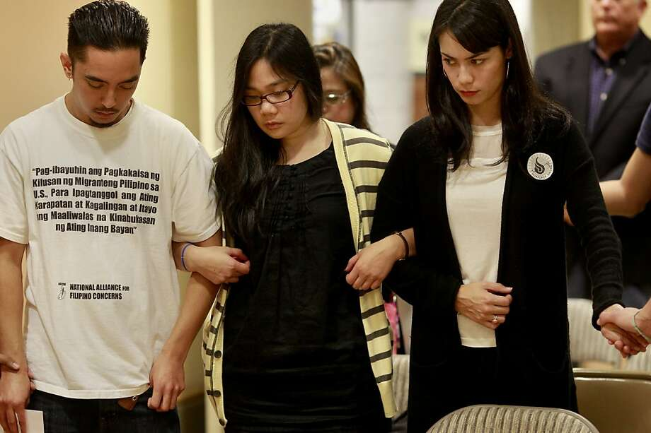 National Alliance for Filipino Concerns members Ryan Leano (left), Darah Macaraeg and Josephina Rubio lock arms as they pray. Photo: Brant Ward, The Chronicle
