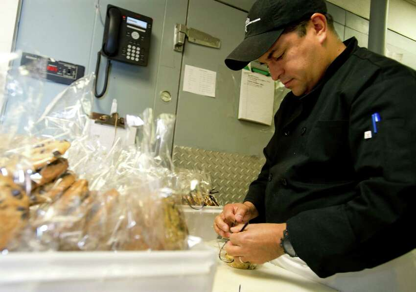 Danny Torres wraps chocolate chip cookies as he prepares for an upcoming gala at Marcia Selden catering in Stamford, Conn., on Wednesday, November 13, 2013.