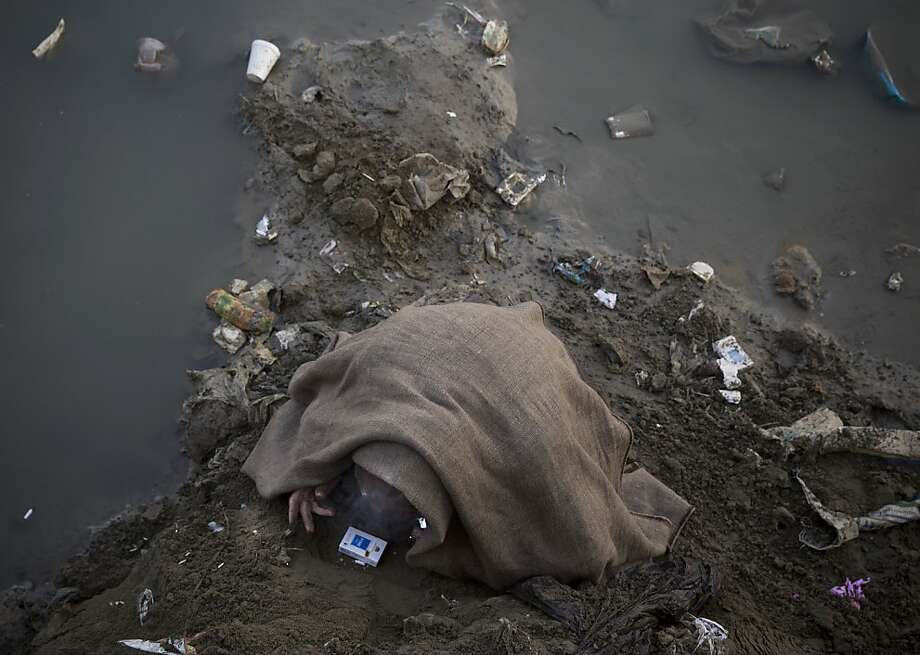 A junkie hides beneath a dirty woolen blanket as he smokes opium in the mud of a foul-smelling river bed in 
