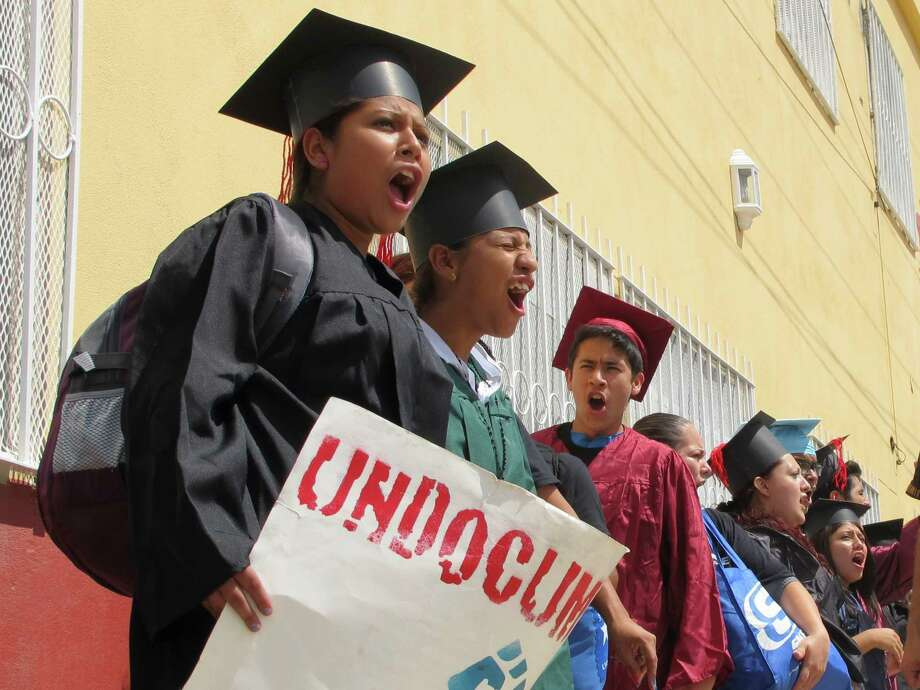 """Wearing graduation-style caps and gowns, Mexican youth raised in the U.S, chant slogans outside a migrant shelter before crossing the international bridge from Nuevo Laredo, Mexico, Monday Sept. 30, 2013. Wearing a colorful array of graduation-style caps and gowns, 34 young people who spent long stretches of their childhoods in U.S. cities like Phoenix and Boston chanted """"undocumented and unafraid"""" as they crossed the Rio Grande into Texas. (AP Photo/Christopher Sherman) Photo: Christopher Sherman, STF / AP"""