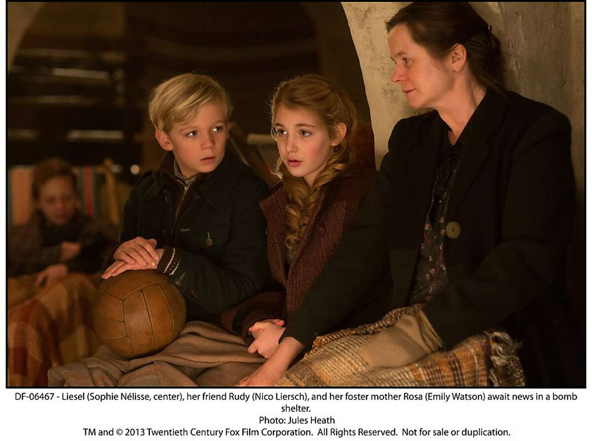 Liesel (Sophie NŽlisse, center), her friend Rudy (Nico Liersch), and her foster mother Rosa (Emily Watson) await news in a bomb shelter.