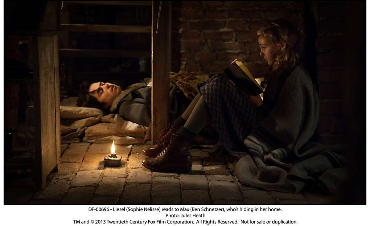 Liesel (Sophie NŽlisse) reads to Max (Ben Schnetzer), who?•s hiding in her home.