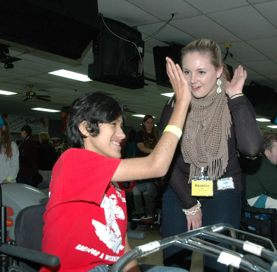 Canyon Lake High student-volunteer Madeline Holder gives Church Hill Middle student Junior Vazquez a high five during Comal ISD's STAR bowling contest. Photo: Courtesy